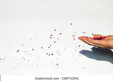 Glitter in hands. Blowing the glitter
