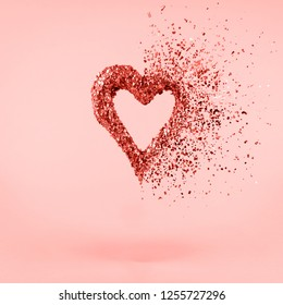 Glitter heart dissolving into pieces on pink background.  Valentines day, broken heart and love emergence concept. Square. Living coral theme - color of the year 2019