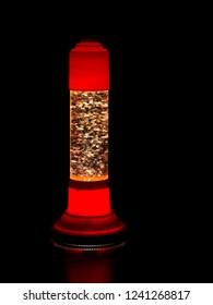 Glitter lava lamp on black background. Genuine vintage 1970 edition, red orange colour.