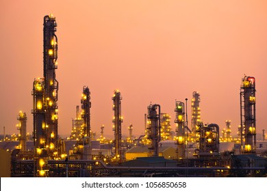 Glitter lighting of petroleum industrial with distillation tower on sunset sky background