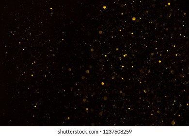 Glitter particles shiny star dust fall on black background
