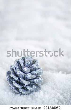 Glitter pinecone on fake snow. Shot with copy space.