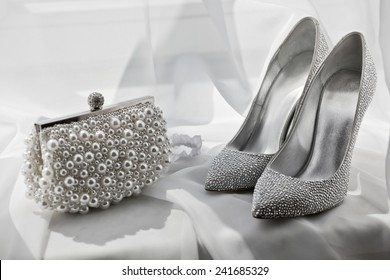 glitter silver shoes and clutch bag on white