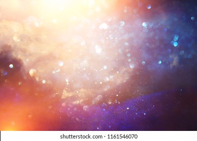 glitter vintage lights background. black, silver, purple and gold. de-focused