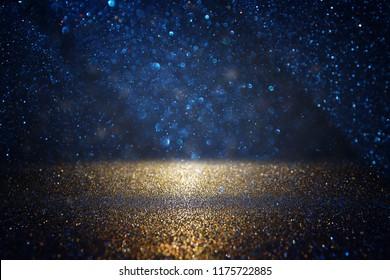 glitter vintage lights background. black, blue and gold. de-focused