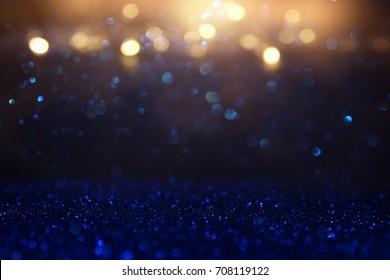 glitter vintage lights background. blue, gold and black. de focused.