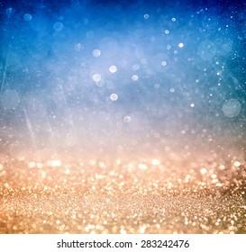 glitter vintage lights background with light burst . silver, blue, gold and white. de-focused.