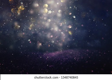 glitter vintage lights background. silver, black, purple and gold. de-focused