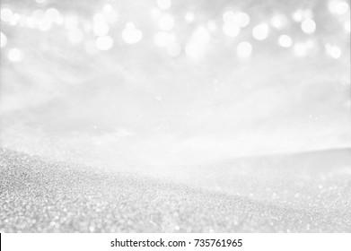 glitter vintage lights background. silver and white. de-focused.
