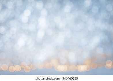 glitter vintage lights background. white, silver,  blue with some warm lights. de-focused. Winter snow and lights.