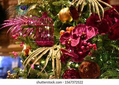Glittering abstract background. Exotic tropical style holiday decorations with artificial purple orchid flowers and palm leaves with sparkling surface. Christmas ornaments. New Year celebration decor