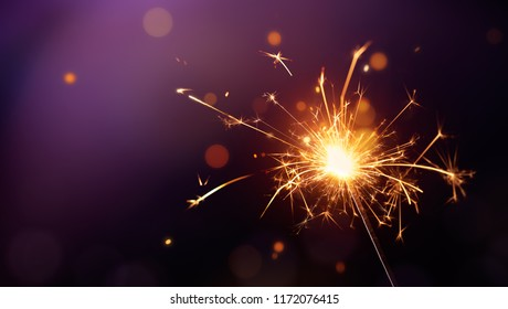 Glittering burning sparkler on purple background