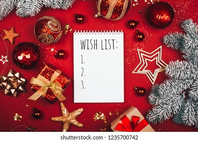 Glittering Christmas decorations and notebook with wish list on red background. Flat lay style. Planning concept.