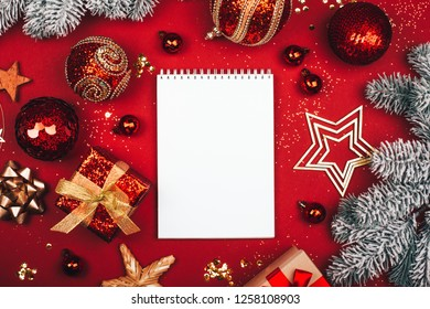 Glittering Christmas decorations and white notebook on red background. Flat lay style. Planning concept.