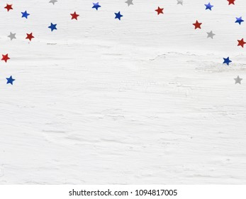 Glittering confetti stars on old grunge wooden background. 4th July, Independence day, card, invitation in usa flag colors. Top view, flat lay, empty space.