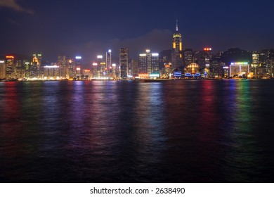 Glittering Hong Kong waterfront at twilight, reflecting in the harbour.