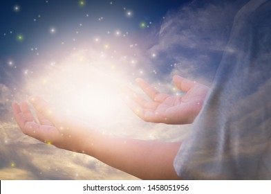 Glittering light and shines through hands of women who raise their hands to pray for God's blessings and sunset background mind sanctification concepts and pure spirit and spirituality forever