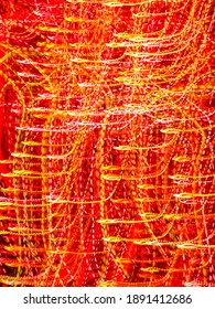 Glittery crisscrossing light trails in an ornamental garden with holiday illumination at night. Long exposure with motion blur. Light painting.