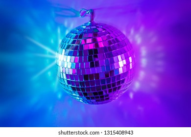 Glittery mirror disco ball on colorful background (purple and blue tonal transitions). Background layout with free text (copy) space.