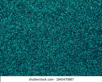 A glittery turquoise paper. Azure glitter light bokeh abstract texture. Pattern designs. Sparkle wallpaper for Christmas. Brilliance shimmering sequin background. Party time.
