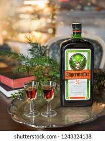 Gliwice. Poland. 11.26.2018. Happy new year or christmas background with Jagermeister alcohol drink, elixir. Bottle of Jagermeister with glasses on a vintage tray on the background of books.