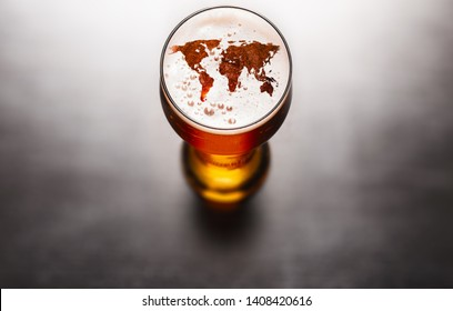 Global beer concept. World map silhouette on foam in beer glass on black table. Elements of this image furnished by NASA