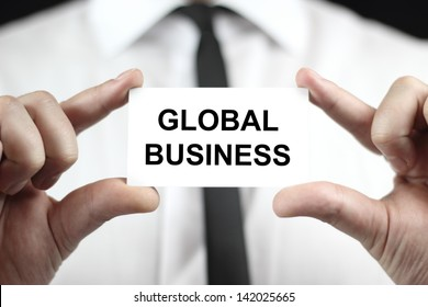 Global Business. Businessman in white shirt with a black tie, shows business card.