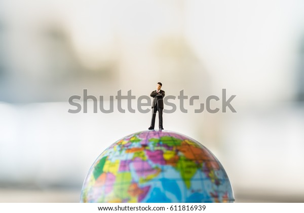 Global and Business Concept. Businessman miniature people figure standing on mini world ball model.