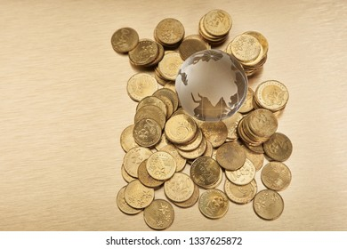 Global economy concept with glass sphere globe and gold colored coins