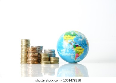 Global economy concept with sphere globe and stacked of coins over white.