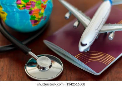 Global Healthcare and travel insurance concept. Passport Stethoscope, airplane and globe on wooden table