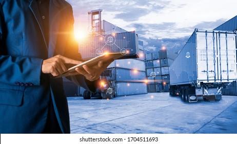 Globale logistische oder logistische Welt. Geschäftsmann oder Geschäftsführer mit Tablet-Stehplatz mit Weltkarte-Symbol und Schiffswerft-Container und LKW-Transporthintergrund. schnelle oder sofortige Versendung.