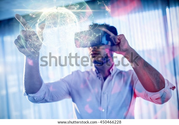 Global technology background in green against businessman using an oculus