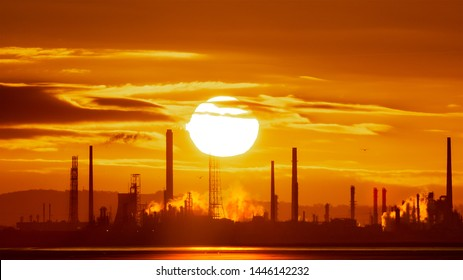 Global Warming Climate Change Concept Epic sunrise at Stanlow Oil Refinery and power plant on the Mersey Estuary Wirral. Greenhouse gas emissions and pollution warm the planet on an industrial dawn.