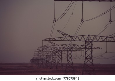 Global warming, climate change. Power line towers in desert on dusk sky background. Electric energy transmission. Electricity distribution stations. Ecology, eco power, technology concept.