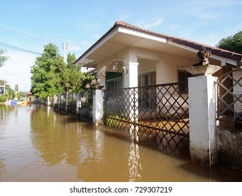 global warming effect in town, low level flood water in urban zone authentic picture shows brown dirty water in abandoned village under frequently repeated high level flood problem in city of THAILAND