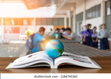 Global world model isolated on opened book with students using technology device background. Technology make people get knowledge as travel around the world.Education,knowledge and reading concept.