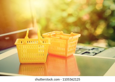 Global or worldwide online shopping / retail ecommerce and delivery service concept : Grocery baskets on a laptop, depicts consumers purchase or order products from online suppliers or digital stores.