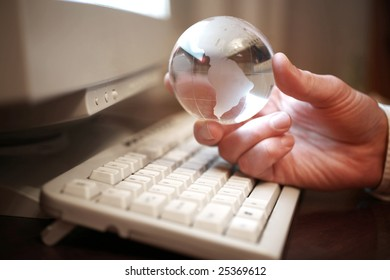 Globe in businessman hand under computer keyboard