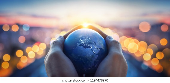 The globe Earth in the hands of man against the night city. Concept on business, politics, ecology and media. Earth day abstract background. Elements of this image furnished by NASA - Shutterstock ID 1194478990