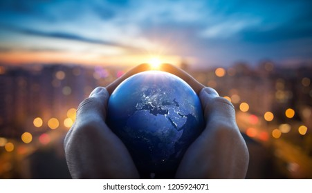 The globe Earth in the hands of man against the night city. Concept on business, politics, ecology and media. Earth day abstract background. Elements of this image furnished by NASA. - Shutterstock ID 1205924071