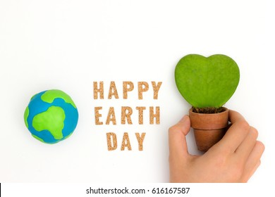 Globe ,earth made from clay, letter happy earth day on white background and hand hold plant heart shape. Concept Save green planet. Earth day holiday eco concept