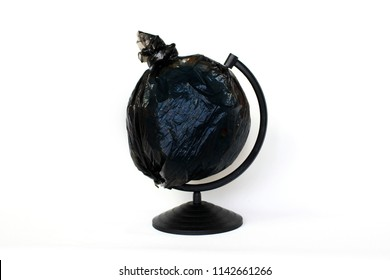 A globe of the earth in a plastic black bag like trash over white background, the concept of ecology problem and World Environment Day. Photo with message for social advertising, place for inscription