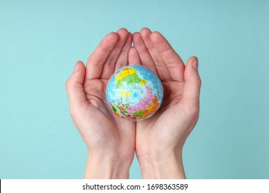 Globe in a female palms on blue background. Planet earth care concept