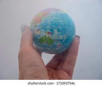 A globe in a human hand against a background of smoke. Concept photo symbolizing environmental pollution.