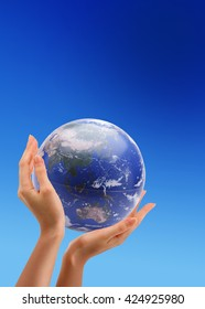 Globe in the human hands over blue sky