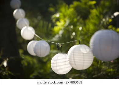 Globe lanterns hanging on a string at a party
