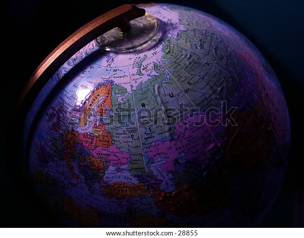 A globe with light cast on its surface, dark shadows.