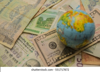 Globe map sign over many american dollar bank notes and bills of different states. international banknotes.