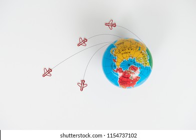 Globe model with air plane paper clip flying circle  on the white background for transport and travel concept